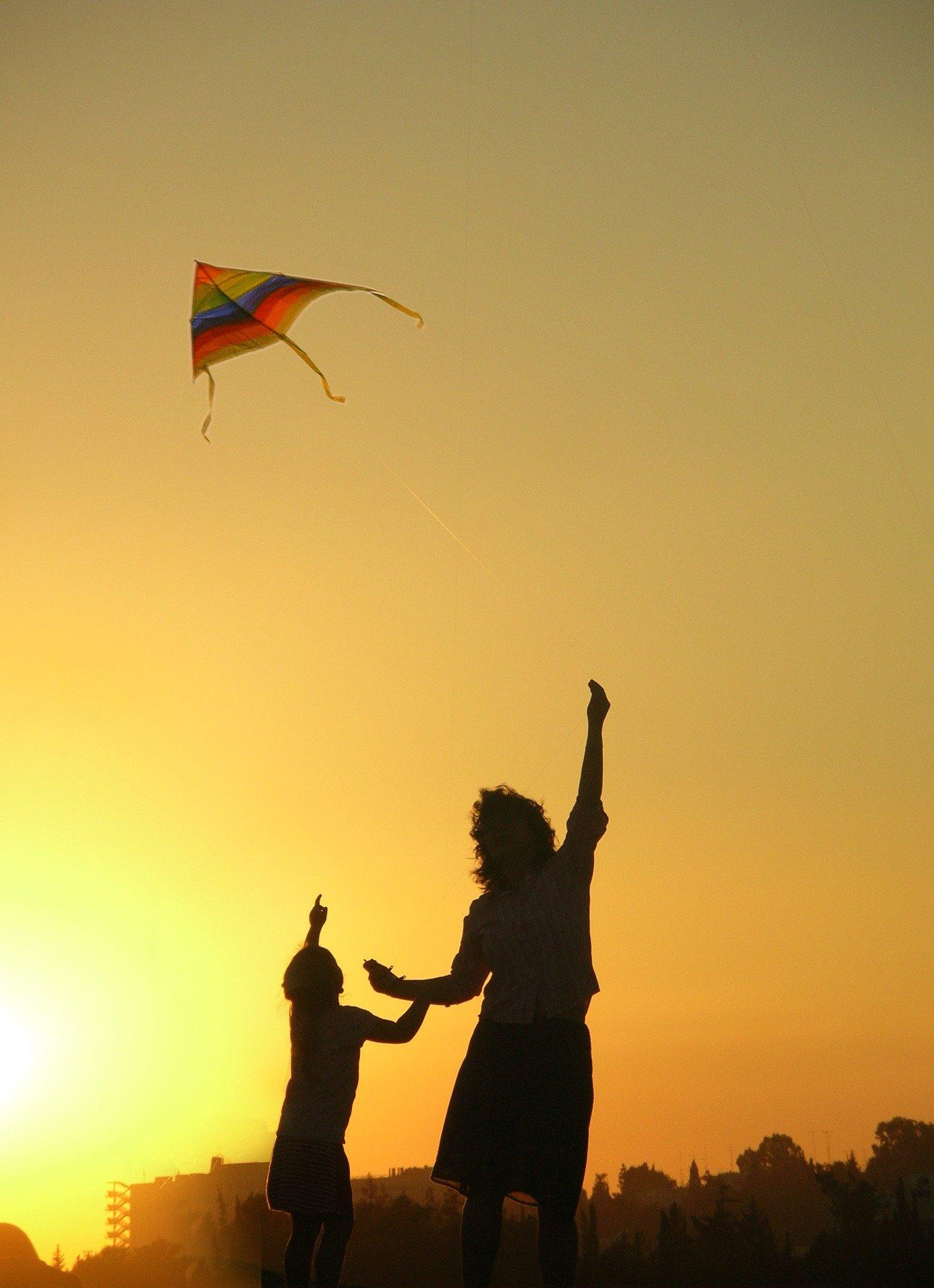 Matka i syn puszczają latawiec na tle zachodzącego słońca. Dzień Matki ma swoją historię już w starożytności.
